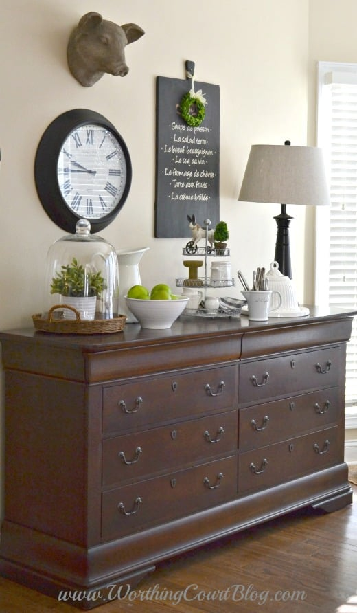 A farmhouse vignette on a dresser used in the kitchen to store linens