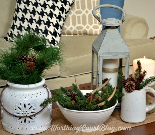 A winter coffee table vignette using evergreens and white