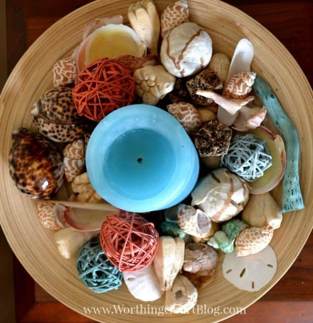 Birdseye view of a bamboo bowl filled with shells, straw orbs and straw orbs