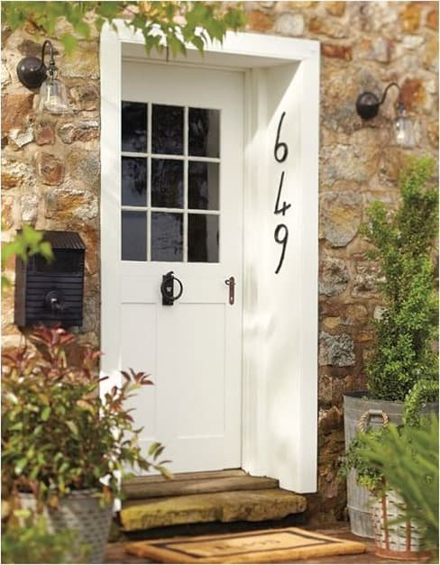 The addition of a great door knocker, oversize house numbers and a mailbox to the side make this inset front door very appealing.