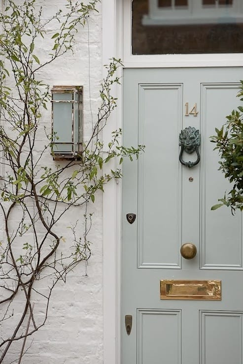 A beautiful grey-green painted front door on a white brick home.