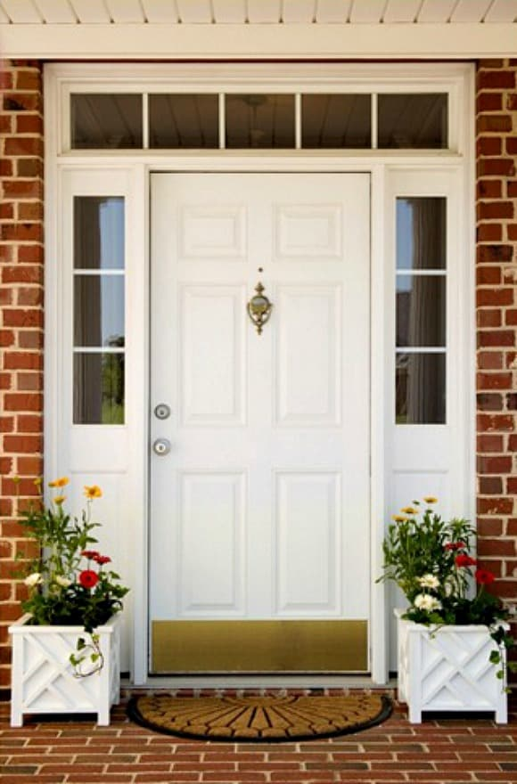 Simple planters and a fresh mat are all that's needed to appreciate the beauty of a pretty front door and sidelight arrangement