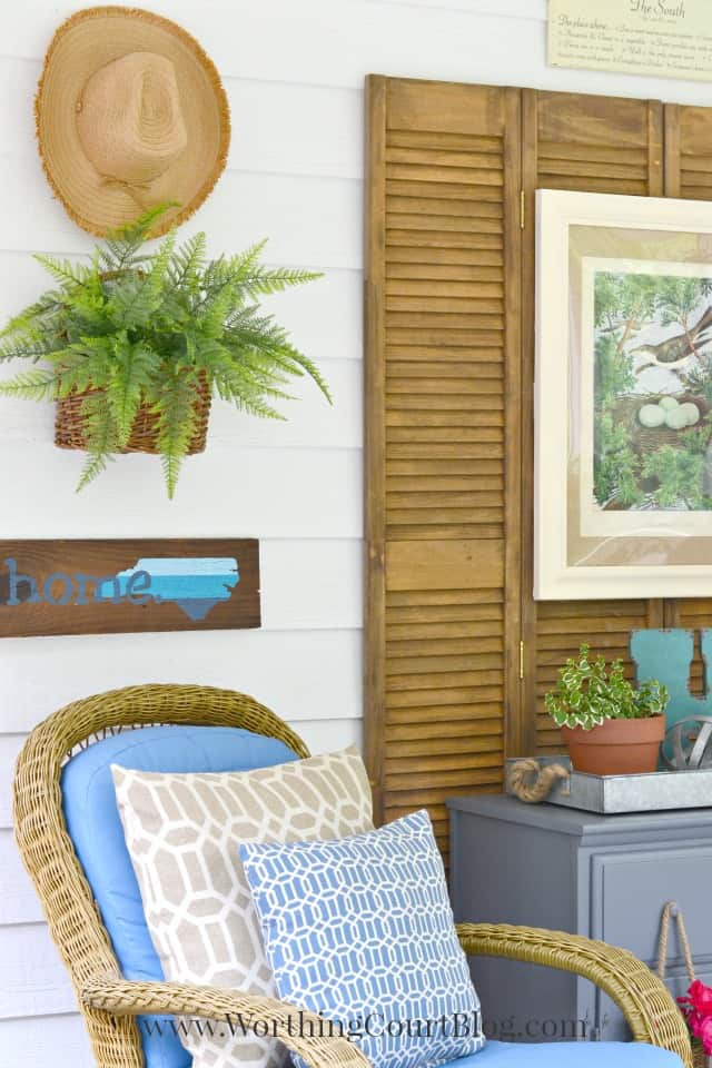 A simple wall collage for outdoors with the gardening hat hanging on the wall.