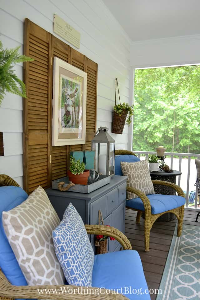 The screened in porch decorated with chairs and blue pillows and artwork.