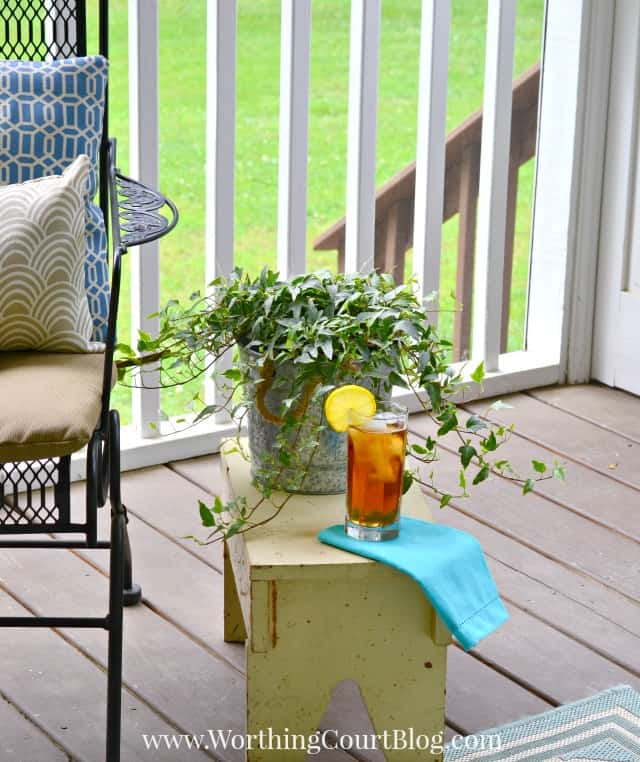 A small stool is beside the chairs on the porch.