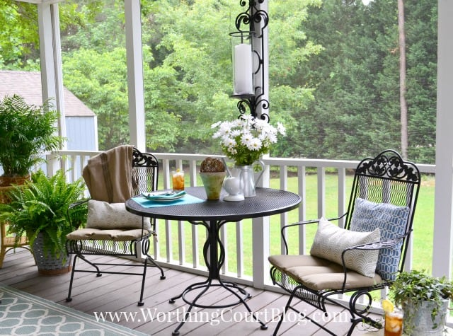 A small wrought iron table and chairs are on the porch.