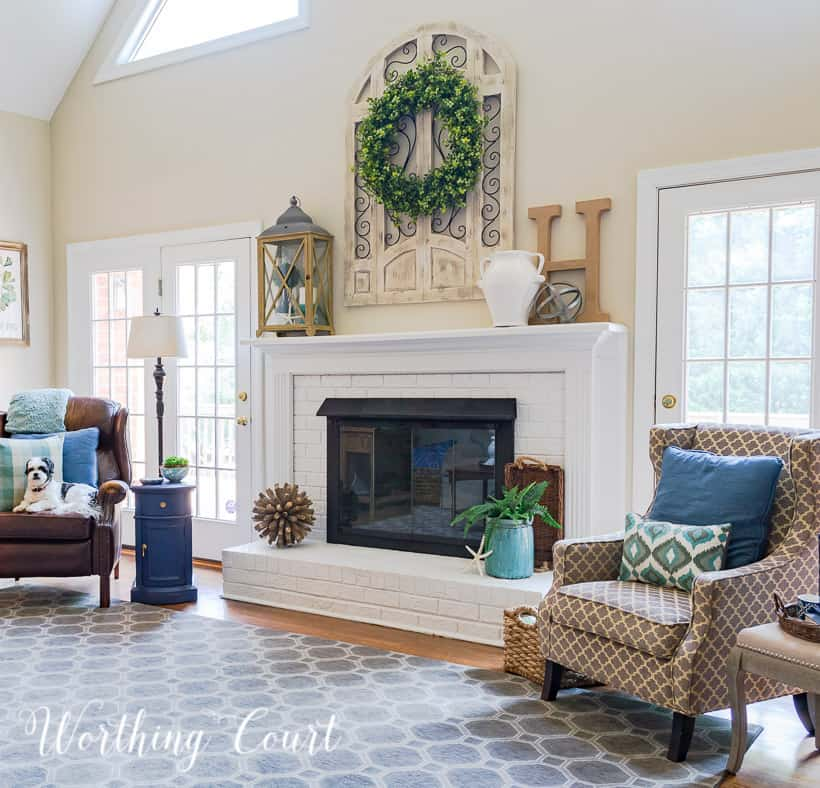 The panted white fireplace with a large green wreath above it.