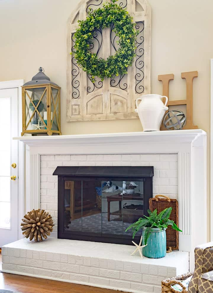 White painted brick fireplace flanked by french doors and arm chairs.