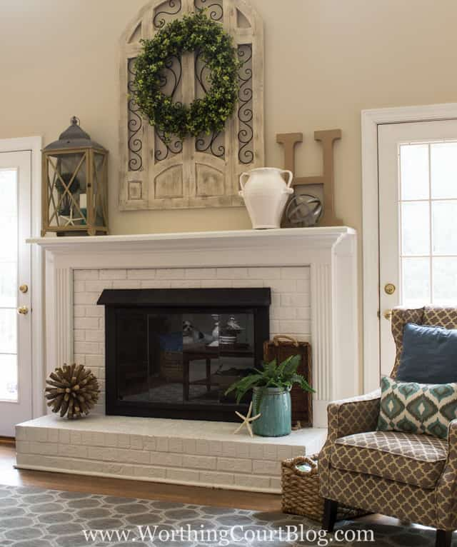red brick fireplace with brown trim painted white and brass fireplace