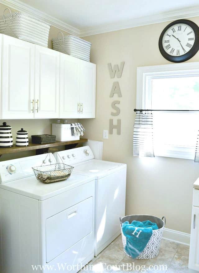 laundry room with white cabinets and white appliances
