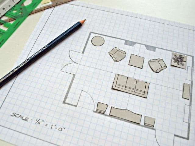 Using small pieces of cardboard cut out in the size of furniture pieces to help plan a furniture arrangement