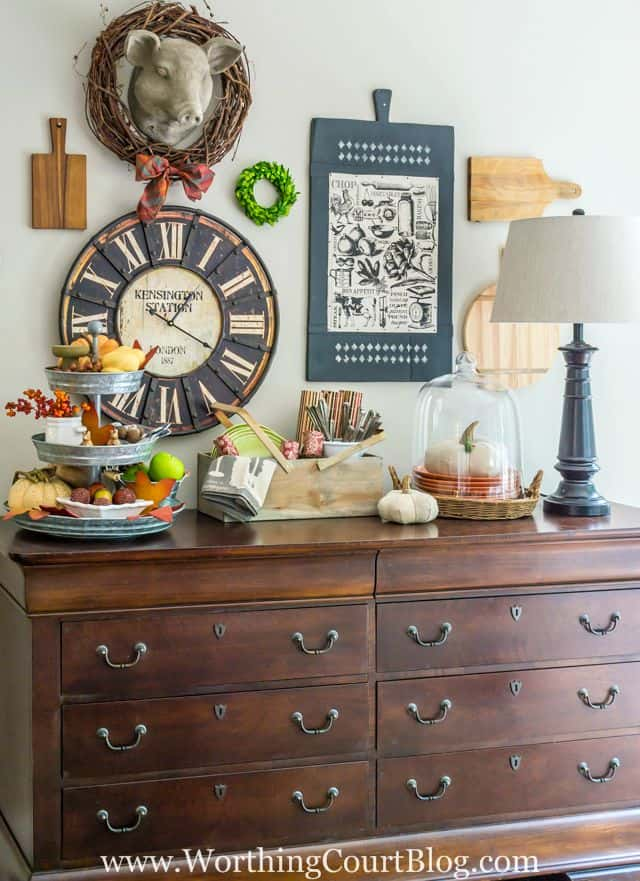 A wooden sideboard with a galvanized treat tray full of pumpkins and gourds.   There is a cloche with a white pumpkin in it.