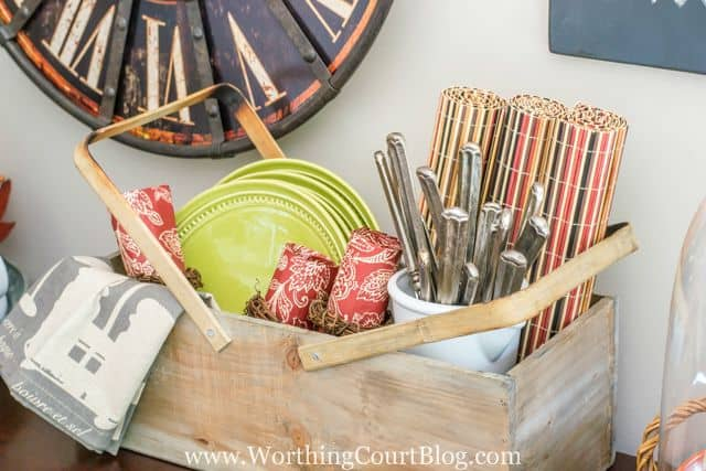 A wooden picnic basket filled with plates, cutlery, and napkins for a fall picnic.