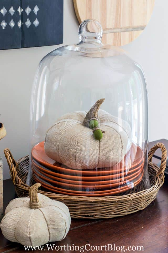A white fabric pumpkin with acorns around the stem under the cloche.