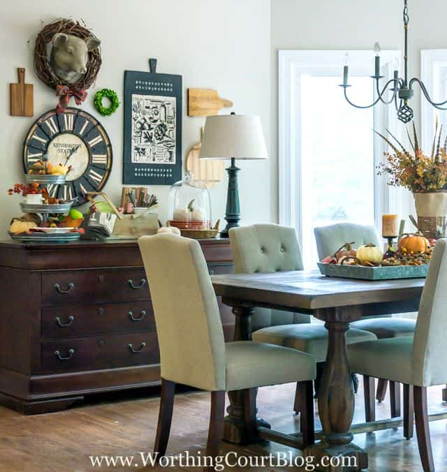 The dining room table with a fall centerpiece in the middle of the table.