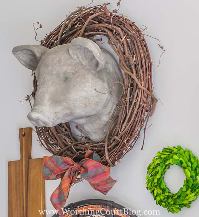 Faux pig head dressed up for fall with a twig wreath and a fall ribbon bow tie