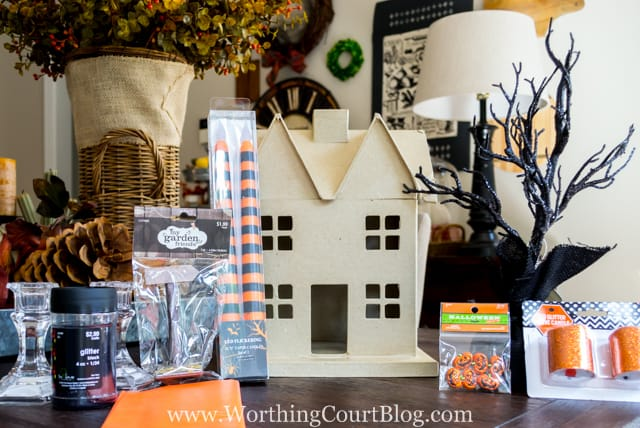 The cardboard house, and all the accessories to make it Halloween on the table.