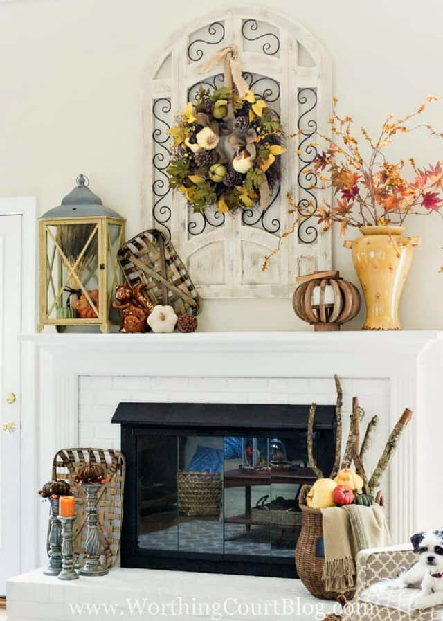 The sitting room fully decorated for fall with a fall wreath, an urn filled with leaves and candlesticks with twig pumpkins.