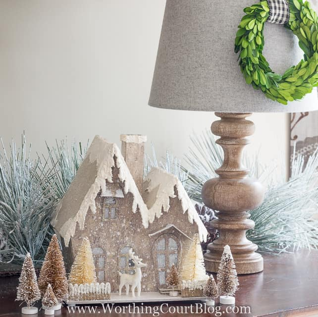 A glittery Christmas house is on the sideboard.
