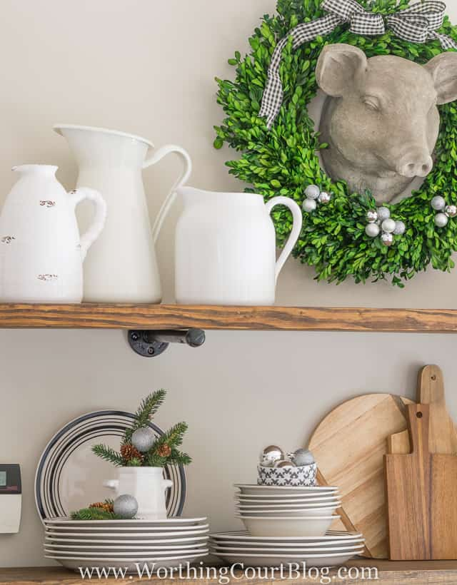 Rustic Farmhouse Kitchen Shelves Decorated For Christmas with a pigs ceramic head and a wreath around it.