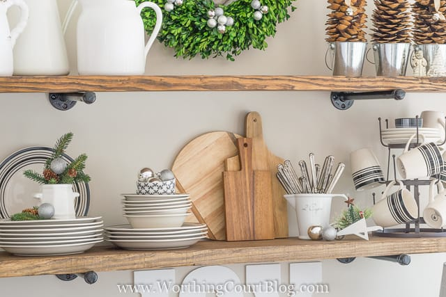 Dishes and cutlery are on the open shelves in the kitchen.