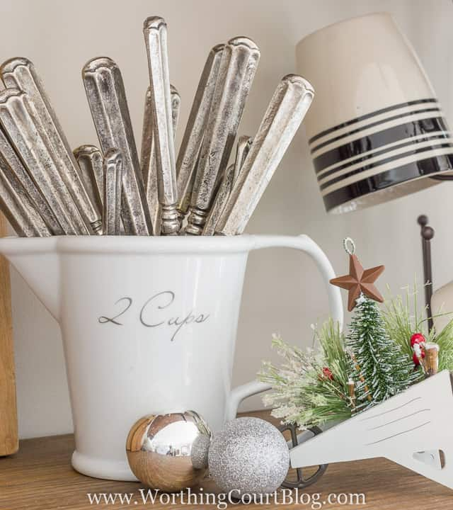 knives are in a white pitcher with silver ornaments beside it.