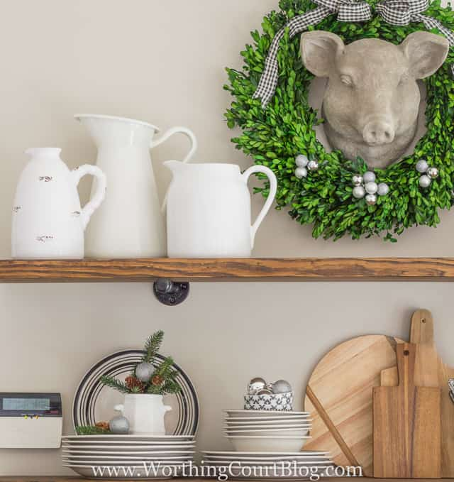 Rustic Farmhouse Kitchen Shelves Decorated For Christmas with white pitches, plates and wooden cutting boards.