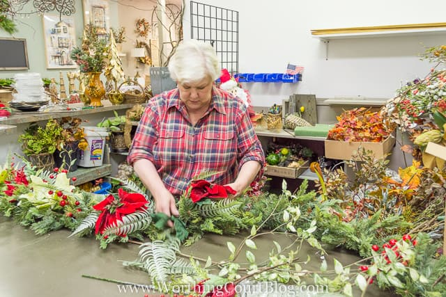 Putting more red flowers into the middle of the garland.