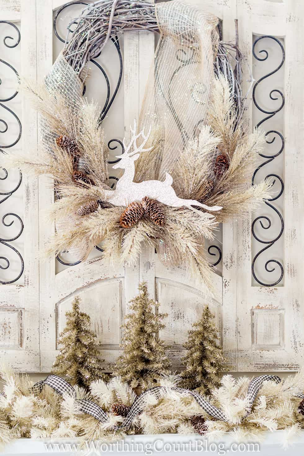 A white deer is on a holiday wreath.
