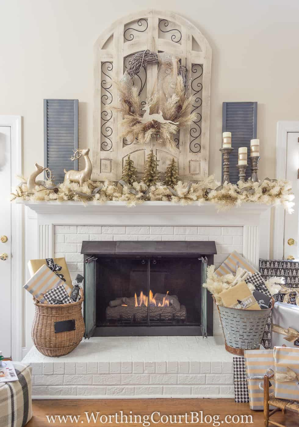 A white fireplace with baskets flanking the sides of it and a mantel decorated for Christmas.