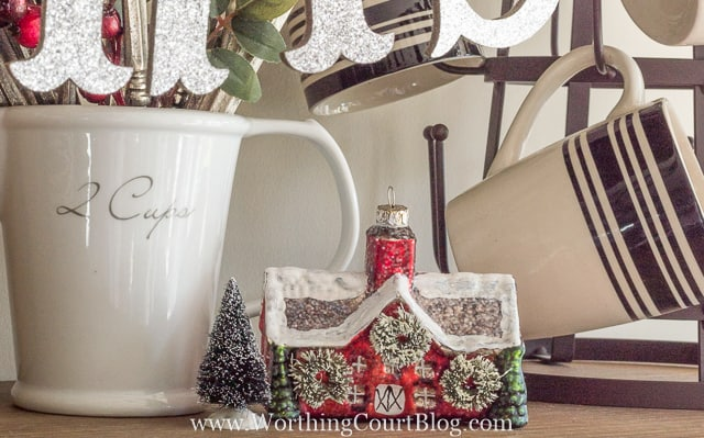 There is a mini house decorated for Christmas porcelain figure on the shelf.