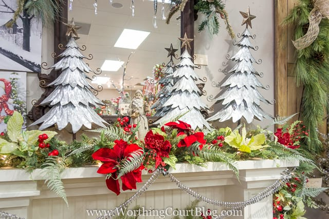 Decorative Christmas trees on the mantel plus red flowers and berries.