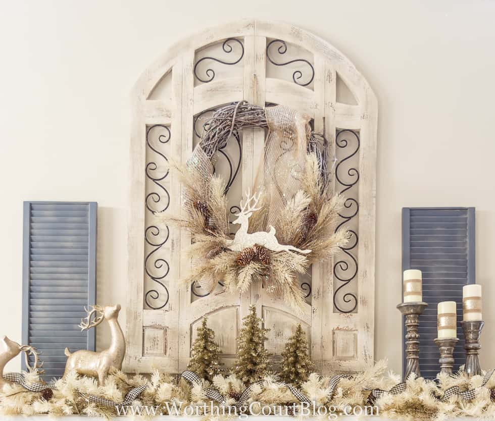 A rustic window frame with a Christmas wreath and deer and candlesticks on the mantel.
