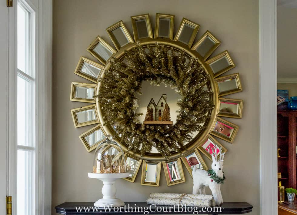 There is a small village in a wreath inside of the mirror.