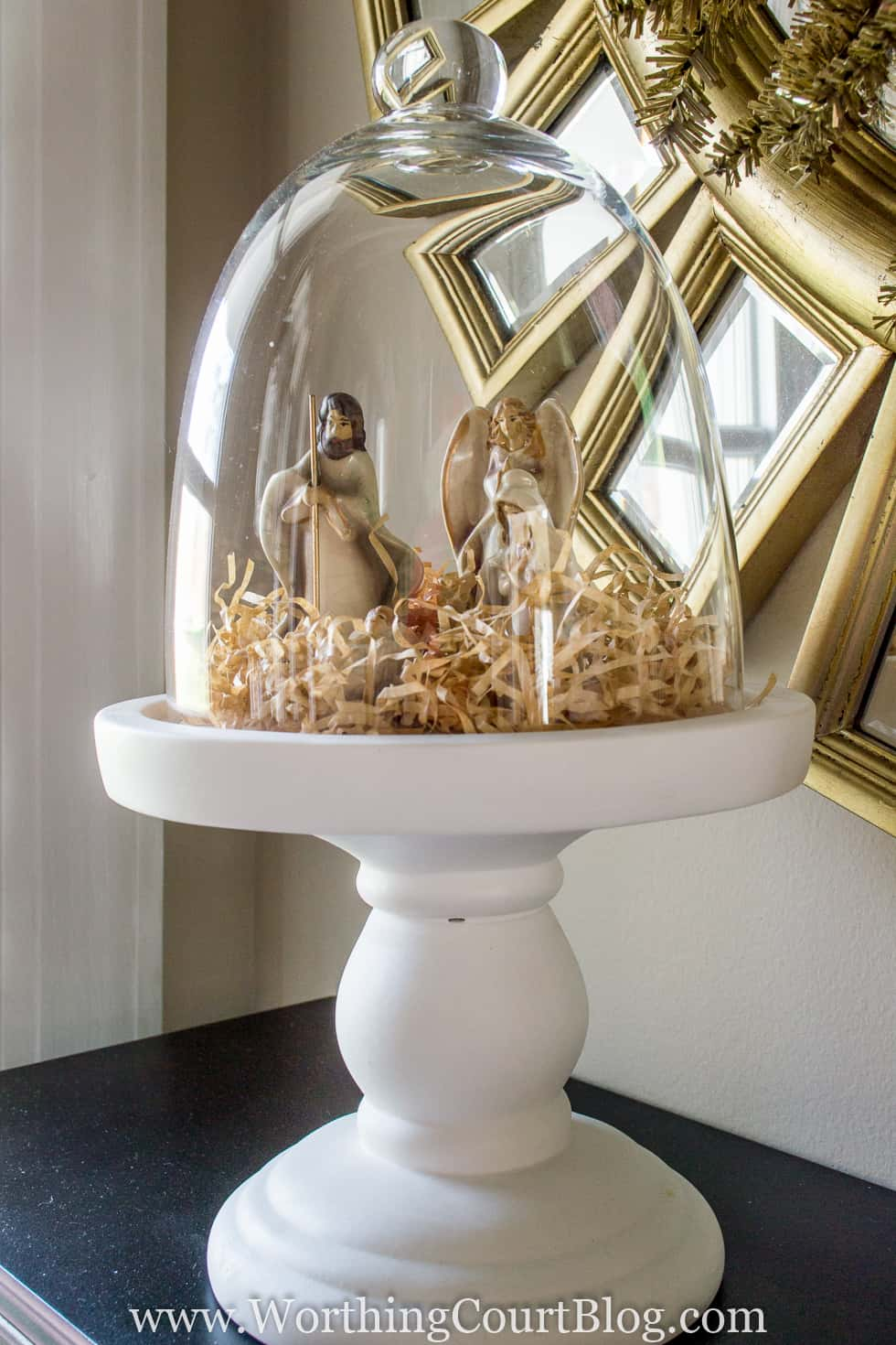 A tiny nativity set is very simply displayed under a glass cloche