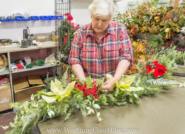 Putting in different types of flowers into the garland.