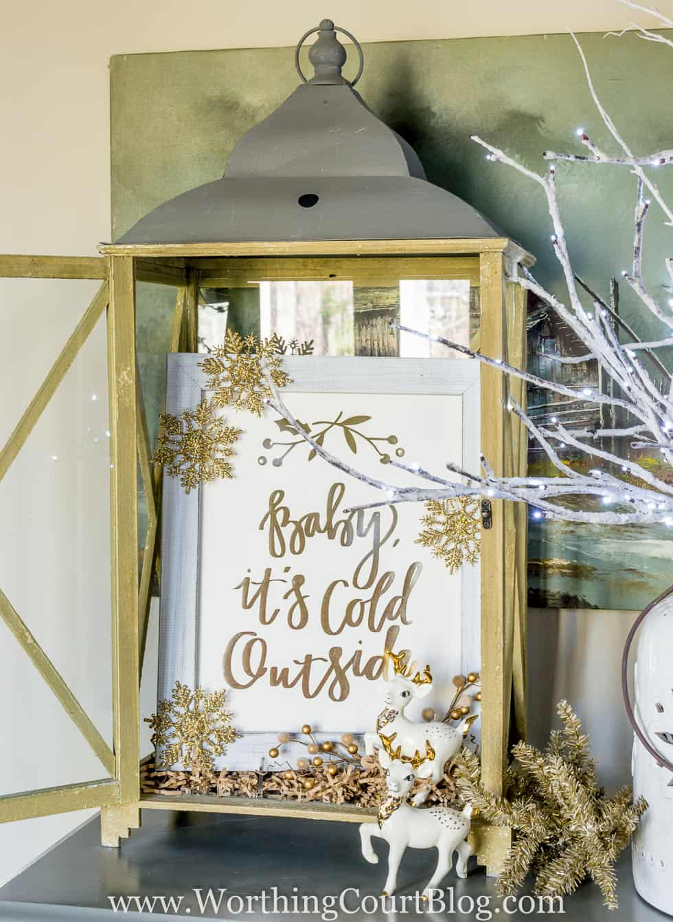'Baby It's Cold Outside' gold foil print from Minted displayed in a rustic lantern