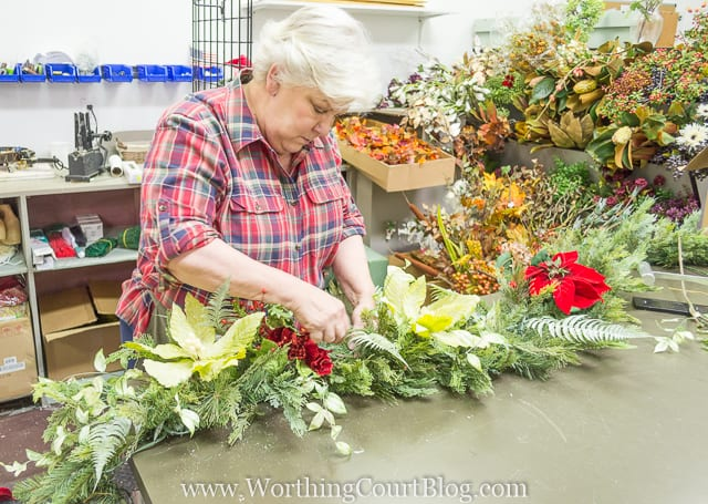 A woman is tucking in all the flowers into the garland.