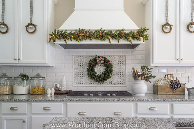 Little wreaths are hanging on the white kitchen cabinets.