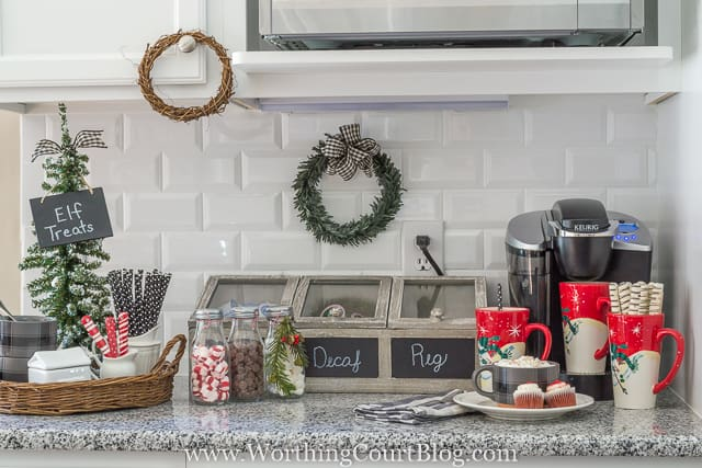 The Keurig coffee maker is in the corner with a mini tree with Elf treats, and holiday cups beside it.