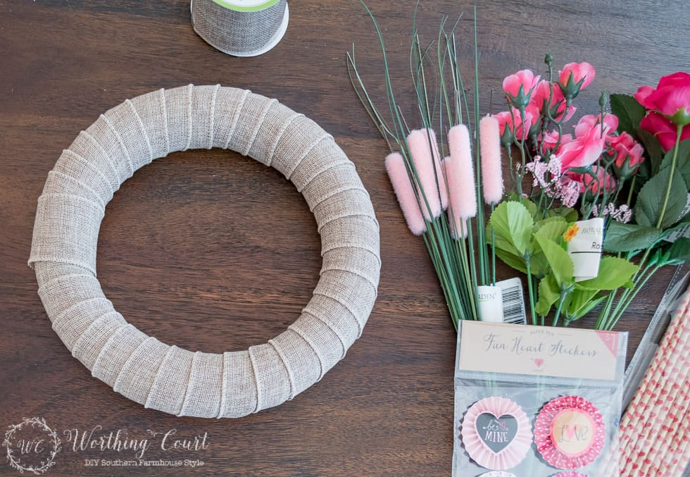 To make a Valentine's Day wreath, wrap the wreath form with burlap ribbon