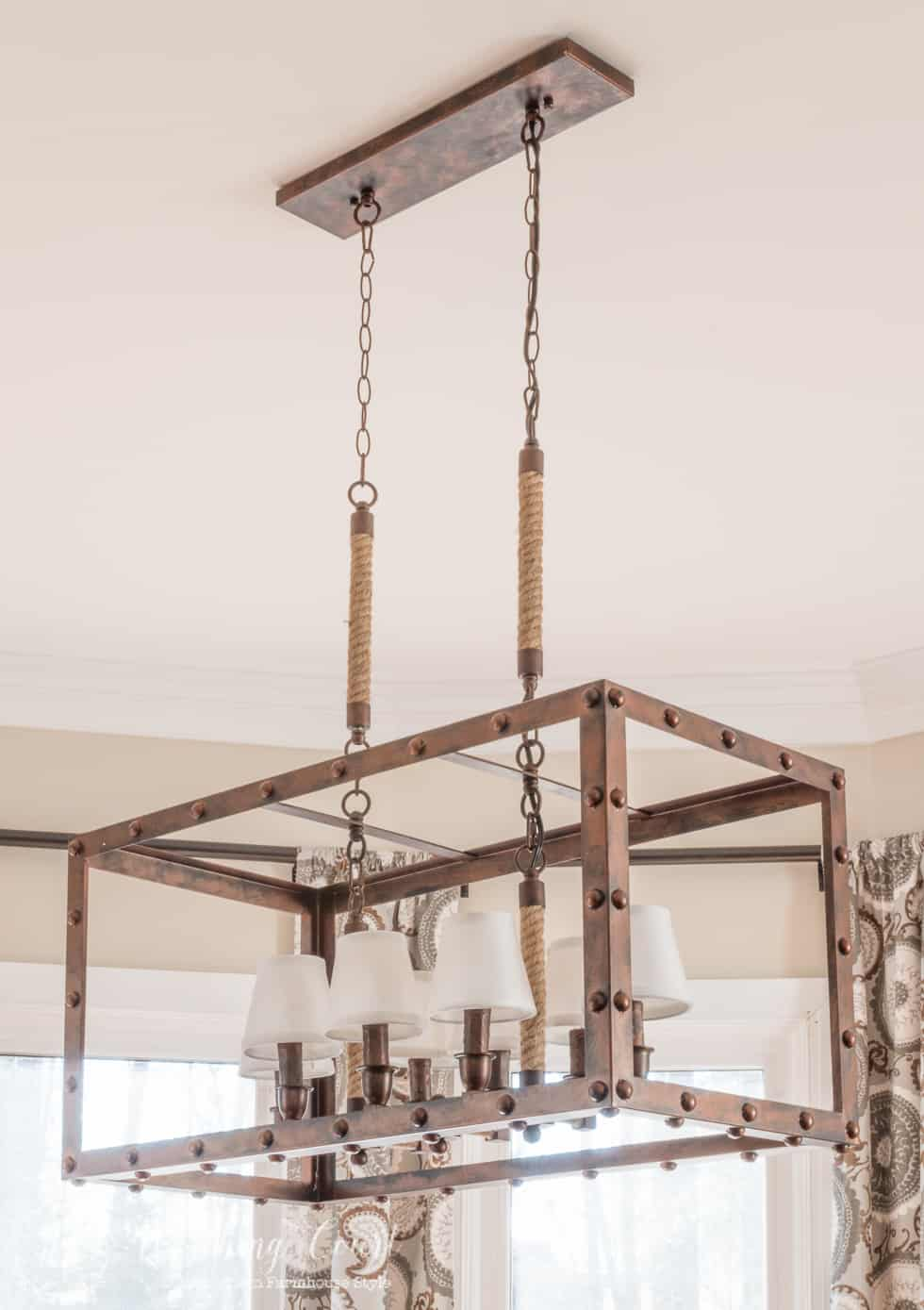 Rustic industrial light fixture in a farmhouse style kitchen breakfast area