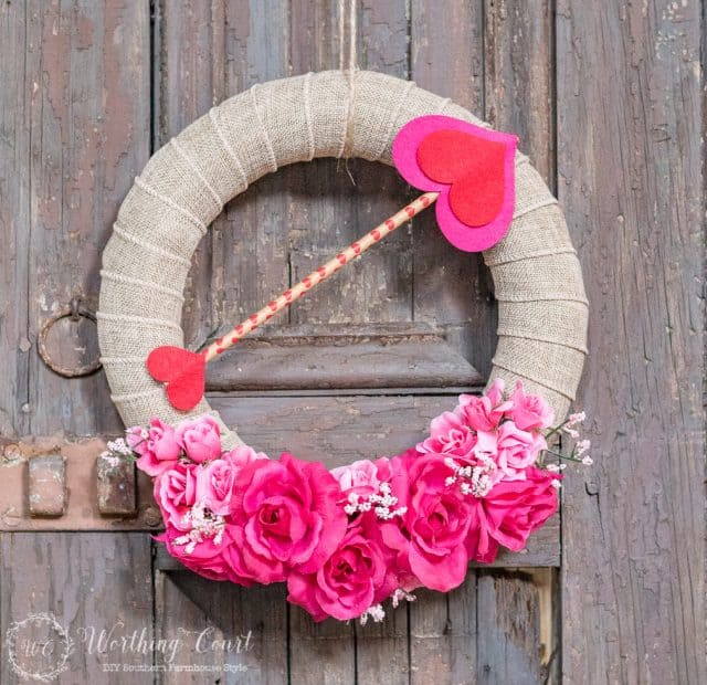 A jute wreath with pink flowers a pink love arrow.