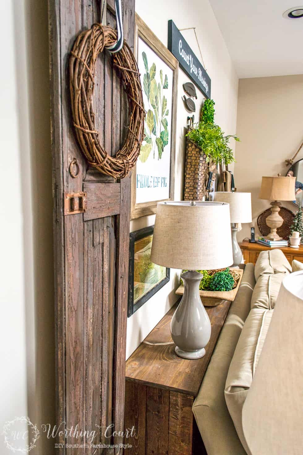 The rustic sofa table with a barn door beside it and a small grey lamp on it.
