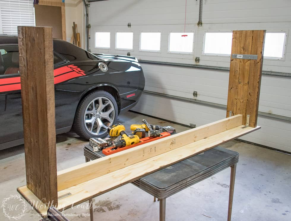 Building the farmhouse table in the garage with a car beside it.
