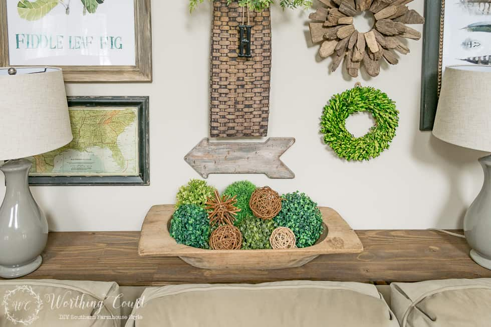 There is a wooden dough bowl on the table filled with greenery and twig balls.