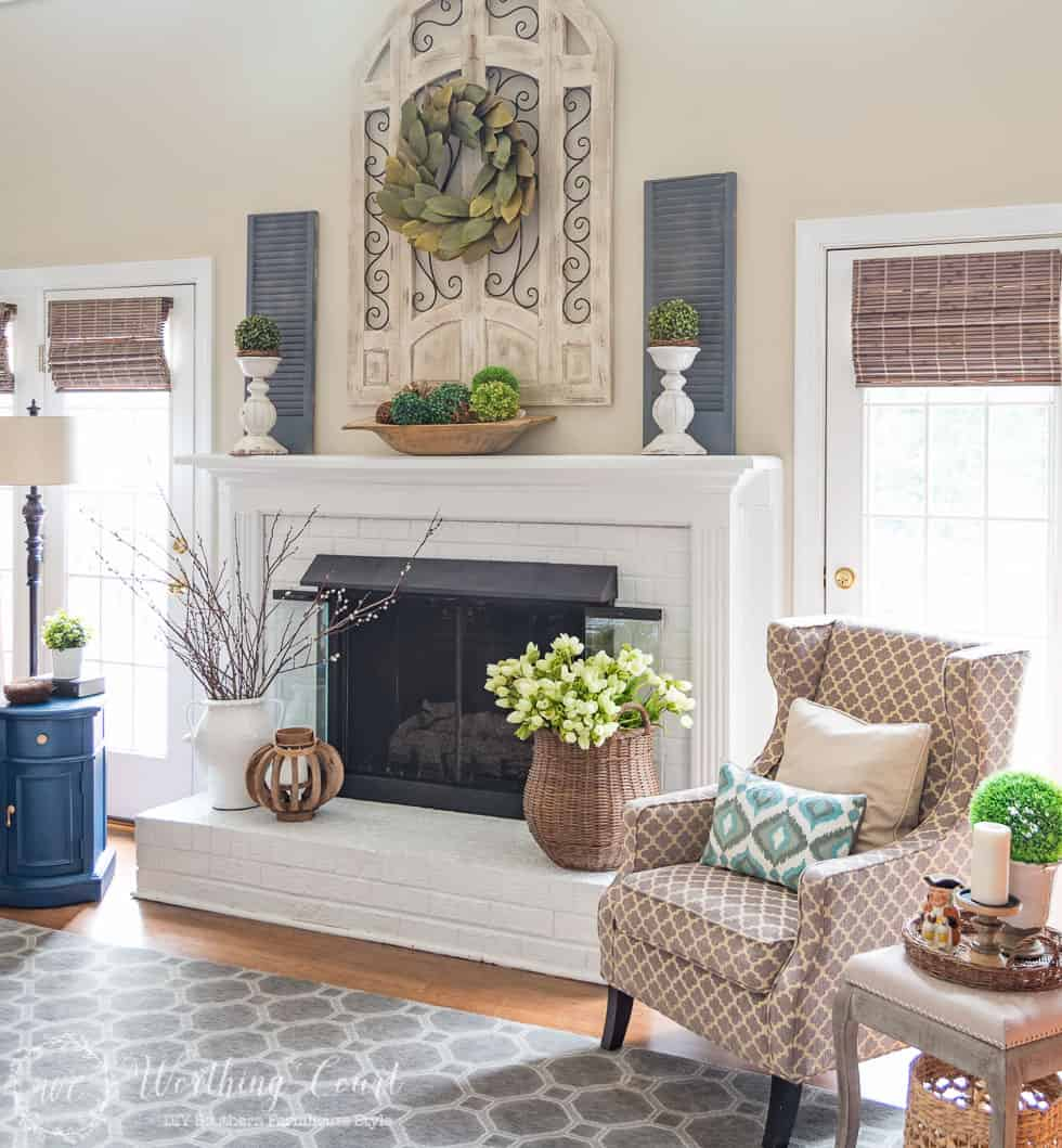 This fireplace celebrates the arrival of spring by filling the mantel and hearth with texture and a mix of real and faux branches and greenery. From a basket overflowing with tulips to an urn filled with pussy willow branches, to a magnolia leaf wreath to an abundance of boxwood orbs, there's no doubt what season it is in this family room.