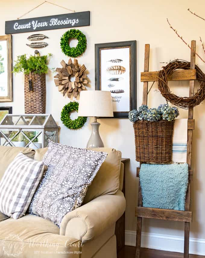 Lighten up a rustic ladder for spring with a pretty blue throw and some dried hydrangeas in hanging basket.