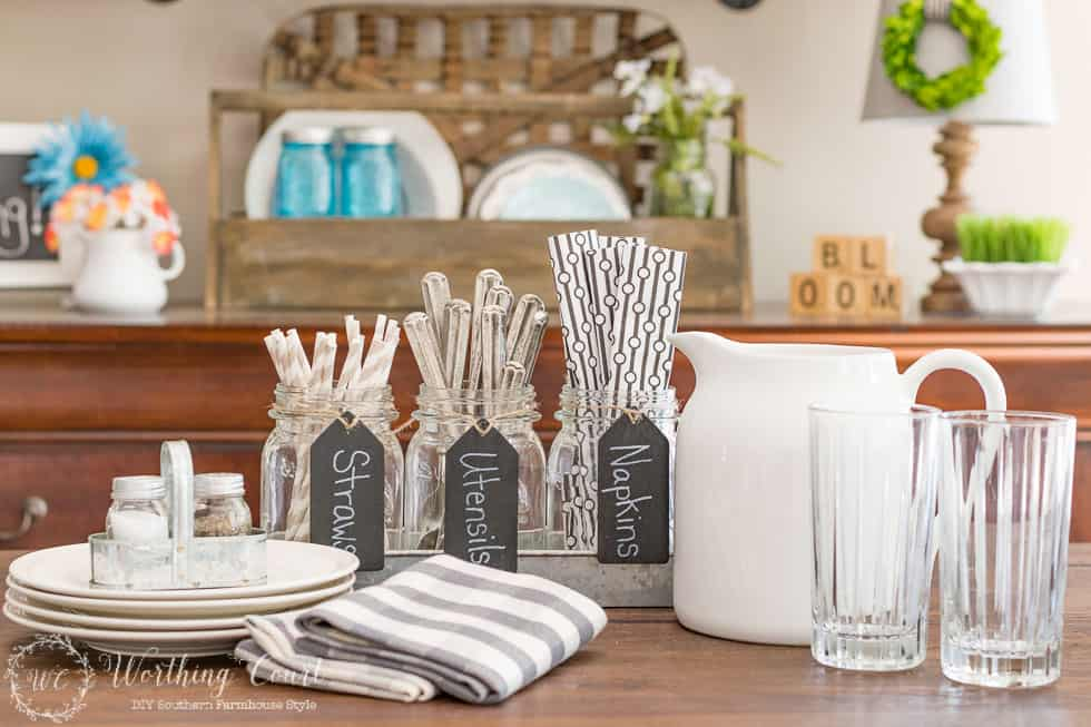 A set of mason jars nestled in a galvanized metal tray pulls double duty as a utensil holder.