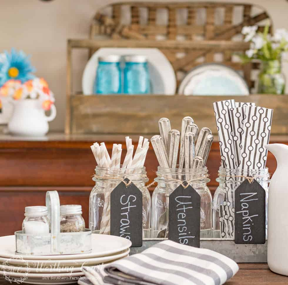 A set of mason jars nestled in a galvanized metal tray pulls double duty as a utensil holder once it's no longer needed as a planter.